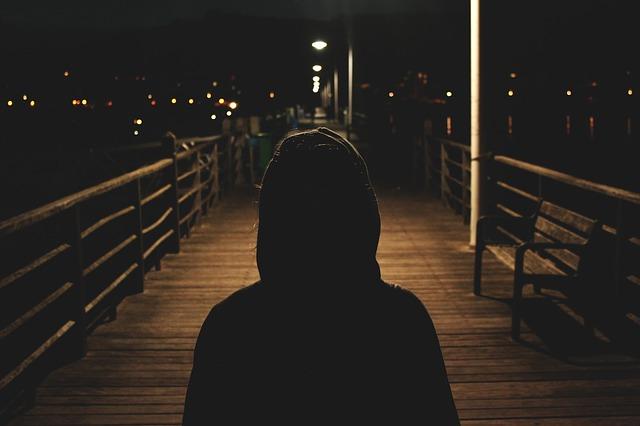 夜、光を追って進む男
